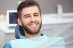 The young man can confidently smile after the dental procedure.