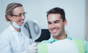 The dentist gives the mirror to the patient after dental treatment.