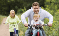 American family fitness enthusiasts. Enjoying the biking experience with the whole family.